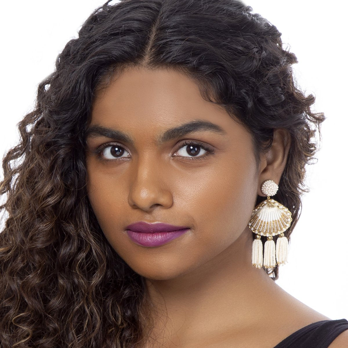 Model wearing handmade gold beaded shell earrings