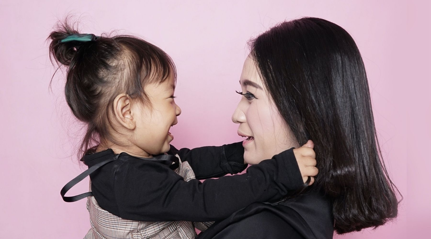 Mother and daughter smiling at each other against a pink background