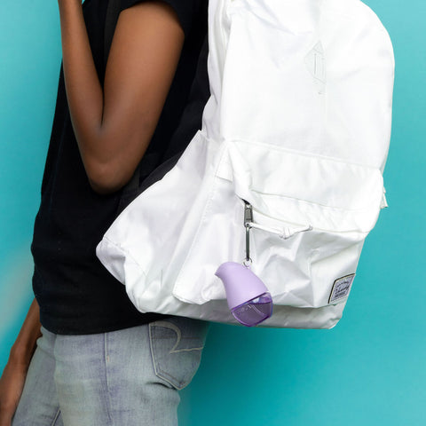 Woman wearing a white backpack with an OLIKA lavender clip on hand sanitizer attached