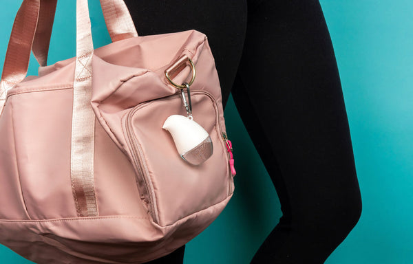 OLIKA Fragrance Free Clip On attached to a pink duffle bag