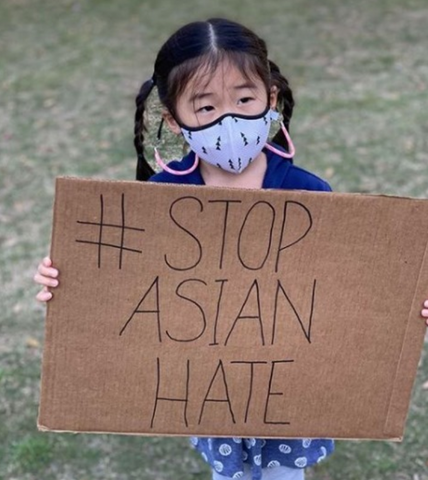 Photo: Girl holding protest sign against Asian Hate