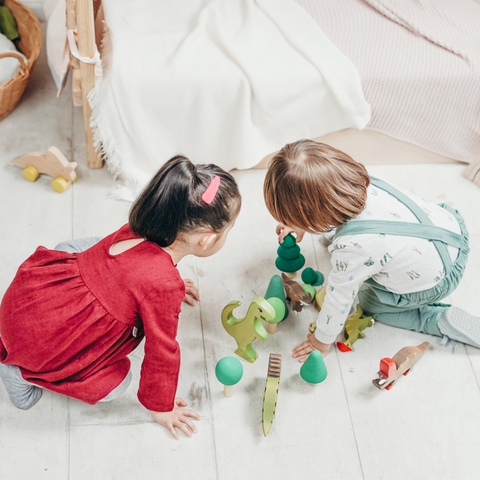 two children playing with brightly colored toys on the floor