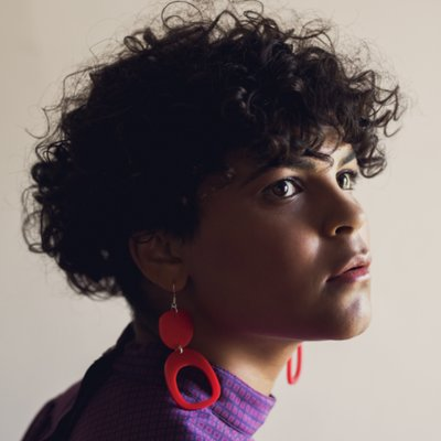 Curly haired person wearing purple turtleneck and red earrings