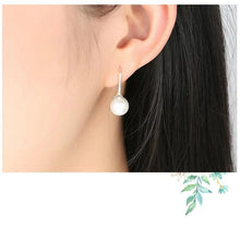 Load image into Gallery viewer, Pearl drop earrings in white on woman