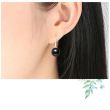 Load image into Gallery viewer, Pearl drop earrings in black on woman