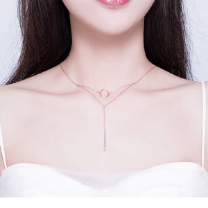 Double layer geometric necklace with a small circle and delicate column in rose gold on woman