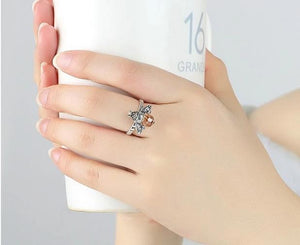 Orange silver bee ring on woman holding a cup
