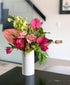 Brighten any room with these bright tropical flowers in a modern textured white vase. Send in Toronto.