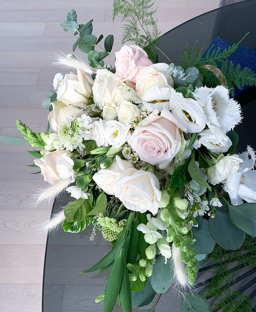 This classic white and green bouquet featuring seasonal flowers is the perfect gift. Toronto delivery available.