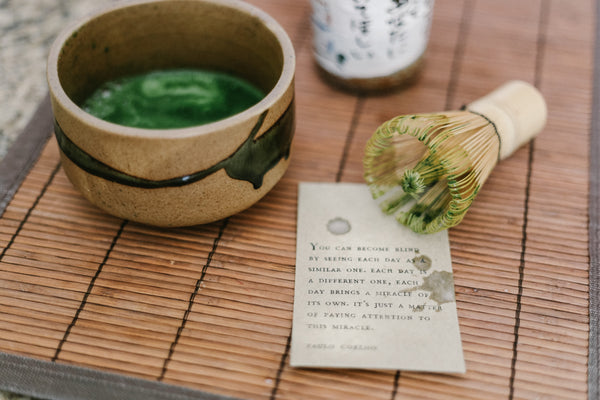 matcha powder and matcha tea with whisk, sitting on table in ceremonial bowl