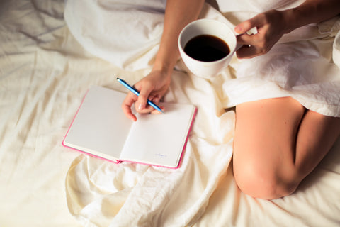 woman writing in her journal while sitting on her bed with a tea in hand