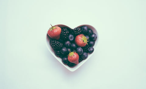 heart with health fruit in it, bowl with healthy strawberries and raspberries in it against a green background