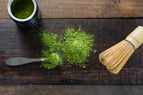matcha powder laid out on a table with matcha measurement spoon and matcha whisk
