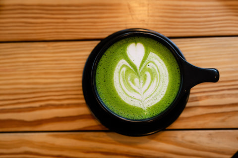 matcha latte with latte artwork sitting on cafe table
