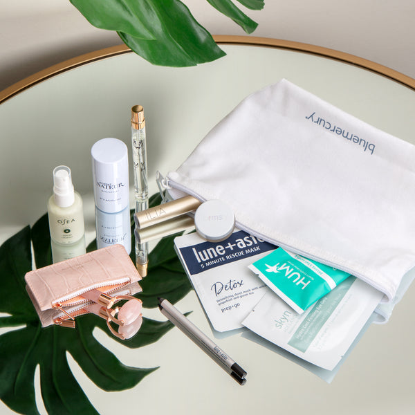 The products from the Bluemercury Conscious Beauty Discovery Set tumbling out of their bag