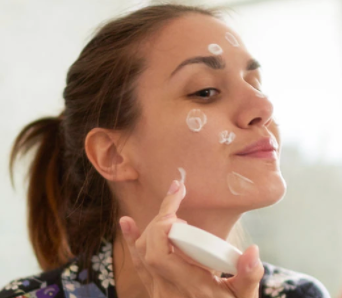 A woman applying face cream in the mirror