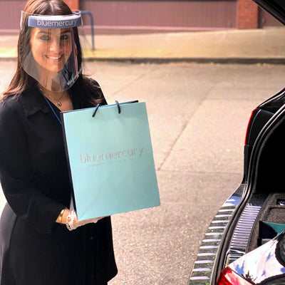A Beauty Expert bringing a Bluemercury shopping bag to a customer's car