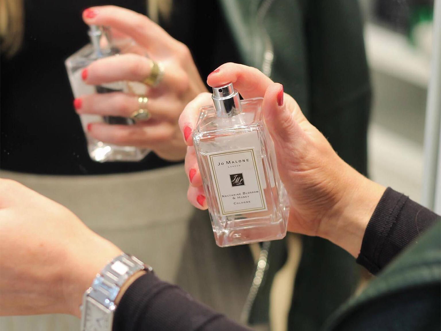Signature Scent event: A woman holds a bottle of Jo Malone Fragrance