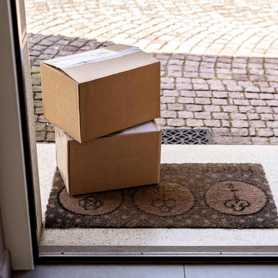 Two boxed packaged sit by a home's open door
