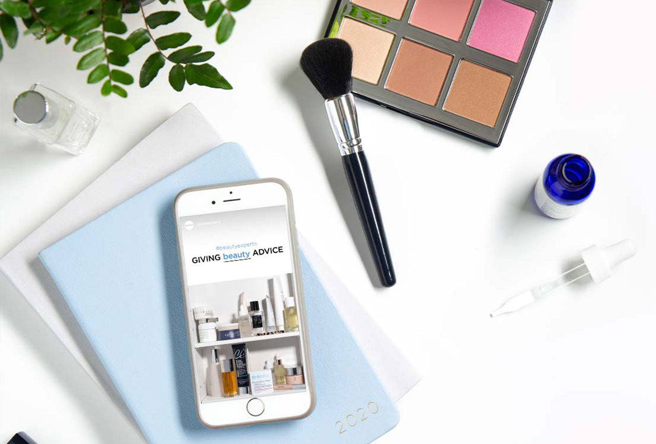 A phone viewing the Giving Beauty Advice page surrounded by makeup and skincare products