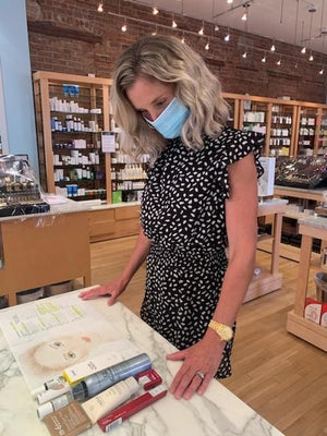 A woman wearing a face mask reviews her face chart and a slew of products