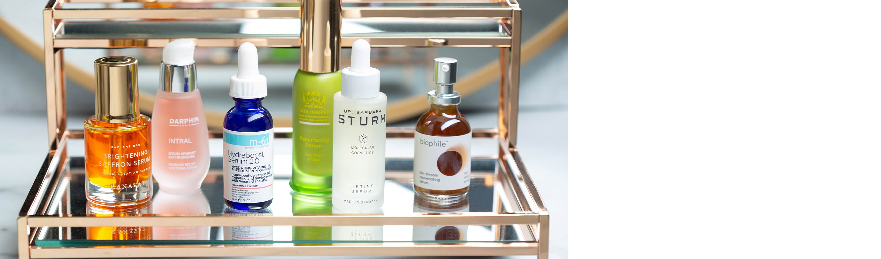 The products from the Serum Buying Guide on a gold and glass shelf