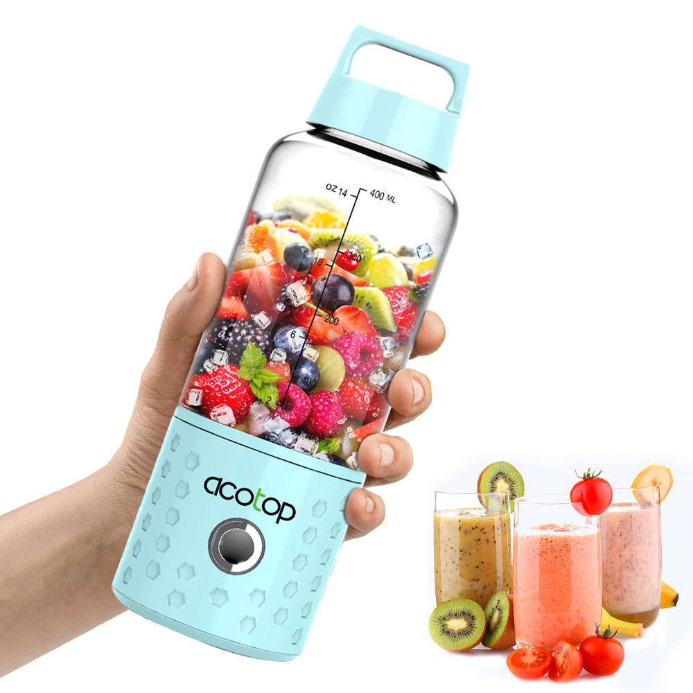 Close up of someone holding the Portable blender with fruit in it on white background. 3 glasses of different fruit smoothes are next to it