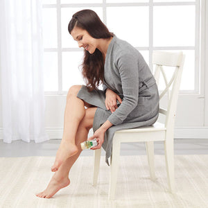 Woman sitting in chair applying Hempvana Heel Tastic to her heel