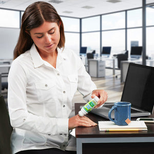 Woman applying Hempvana Cold As Ice to her hand while sitting at a desk