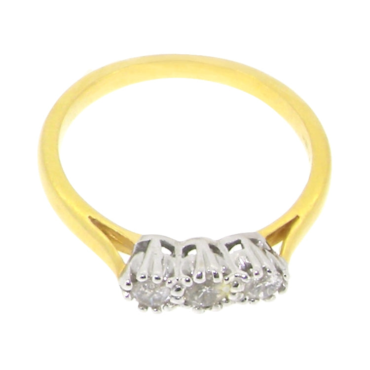 An 18ct yellow and white gold three stone diamond ring, 0.20ct