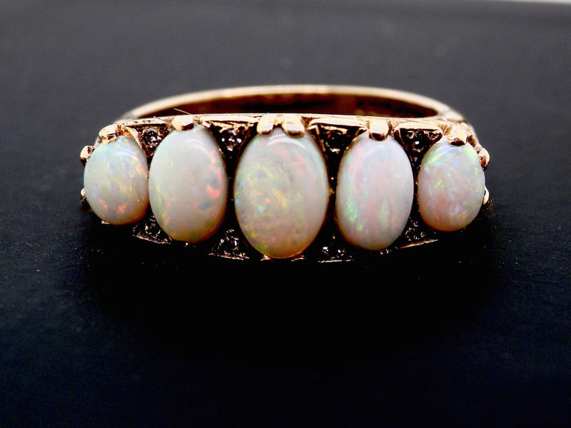A five stone opal dress ring set with small diamonds