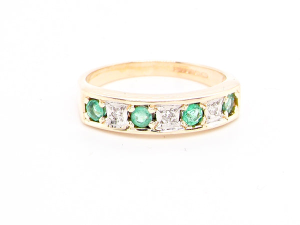 An emerald and diamond half eternity ring