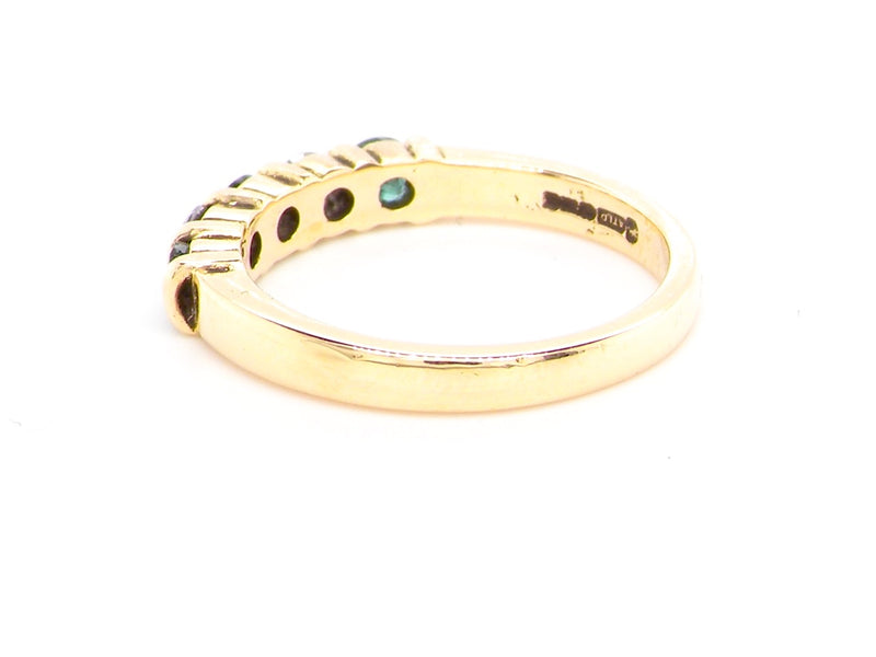 An 18 carat gold emerald and diamond eternity ring