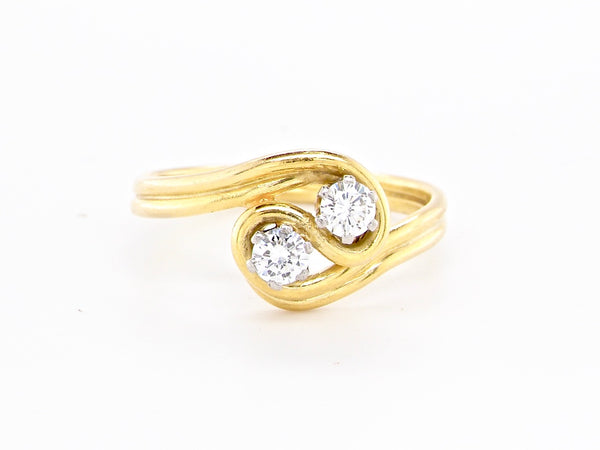 An 18 carat gold two stone diamond cross over toi et moi ring