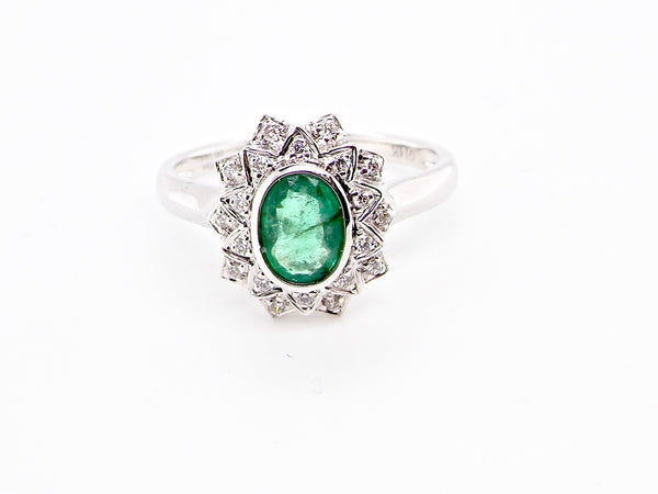 An emerald and diamond white gold cluster ring