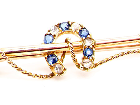 A vintage sapphire and diamond riding crop brooch