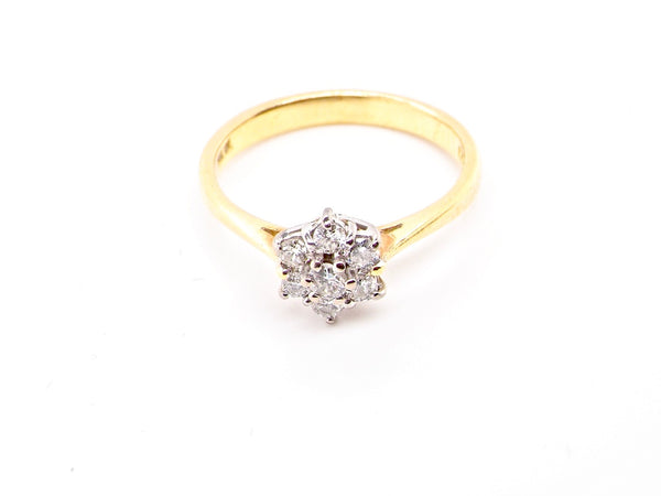 An 18 carat gold traditional diamond cluster ring