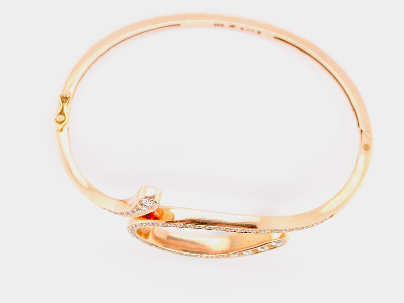 A 14 carat gold diamond loop bangle