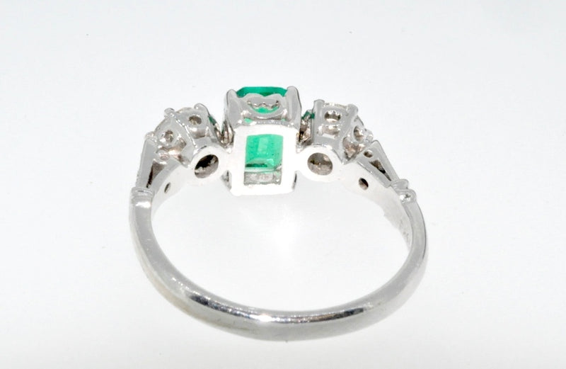 A fine emerald and diamond three stone ring