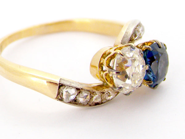 An antique 2 stone sapphire and diamond cross over style ring