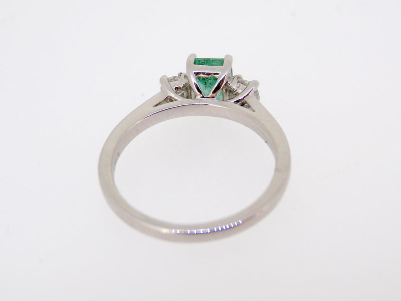 A platinum three stone emerald and diamond ring