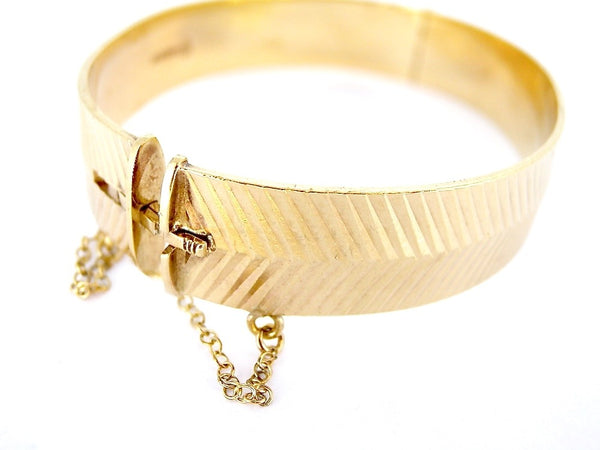 A 9 carat gold diamond cut hinged bangle
