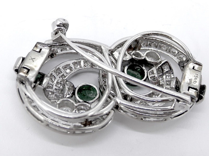 An Art Deco emerald and diamond brooch.