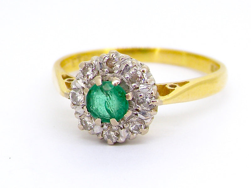 An 18 carat gold emerald and diamond cluster ring