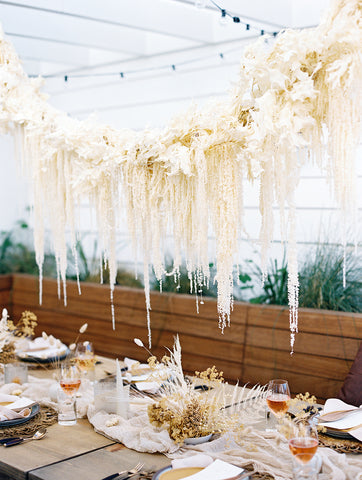 White dired flower hanging installation cloud over a wedding table