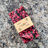 Cherry patterned beeswax wrap folded in an eco-friendly package sleeve