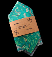 Green patterned beeswax wrap folded in an eco-friendly package sleeve