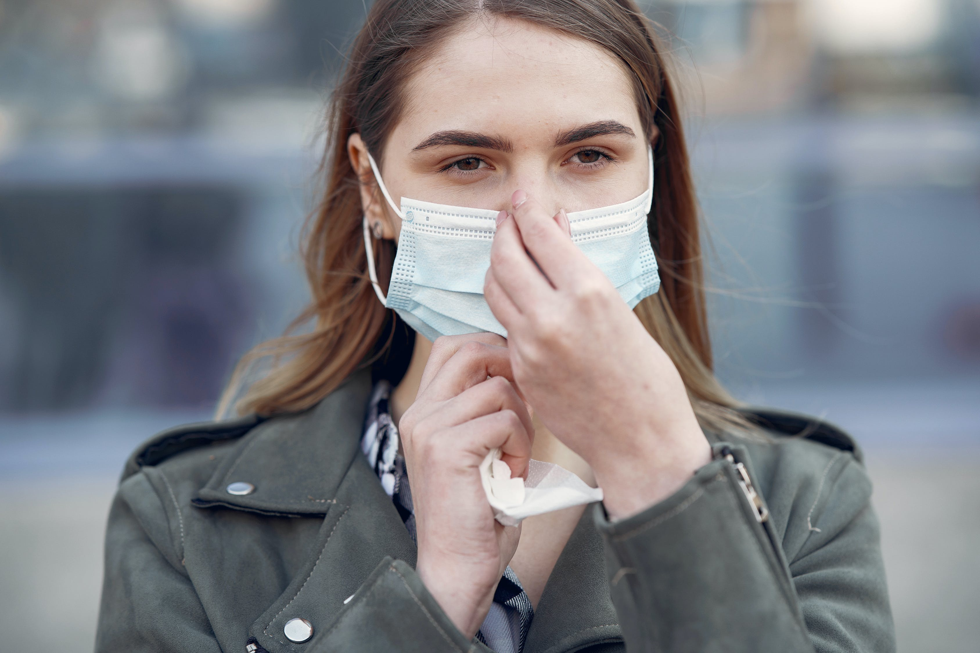 woman wearing non surgical face mask pinching bridge of nose to secure