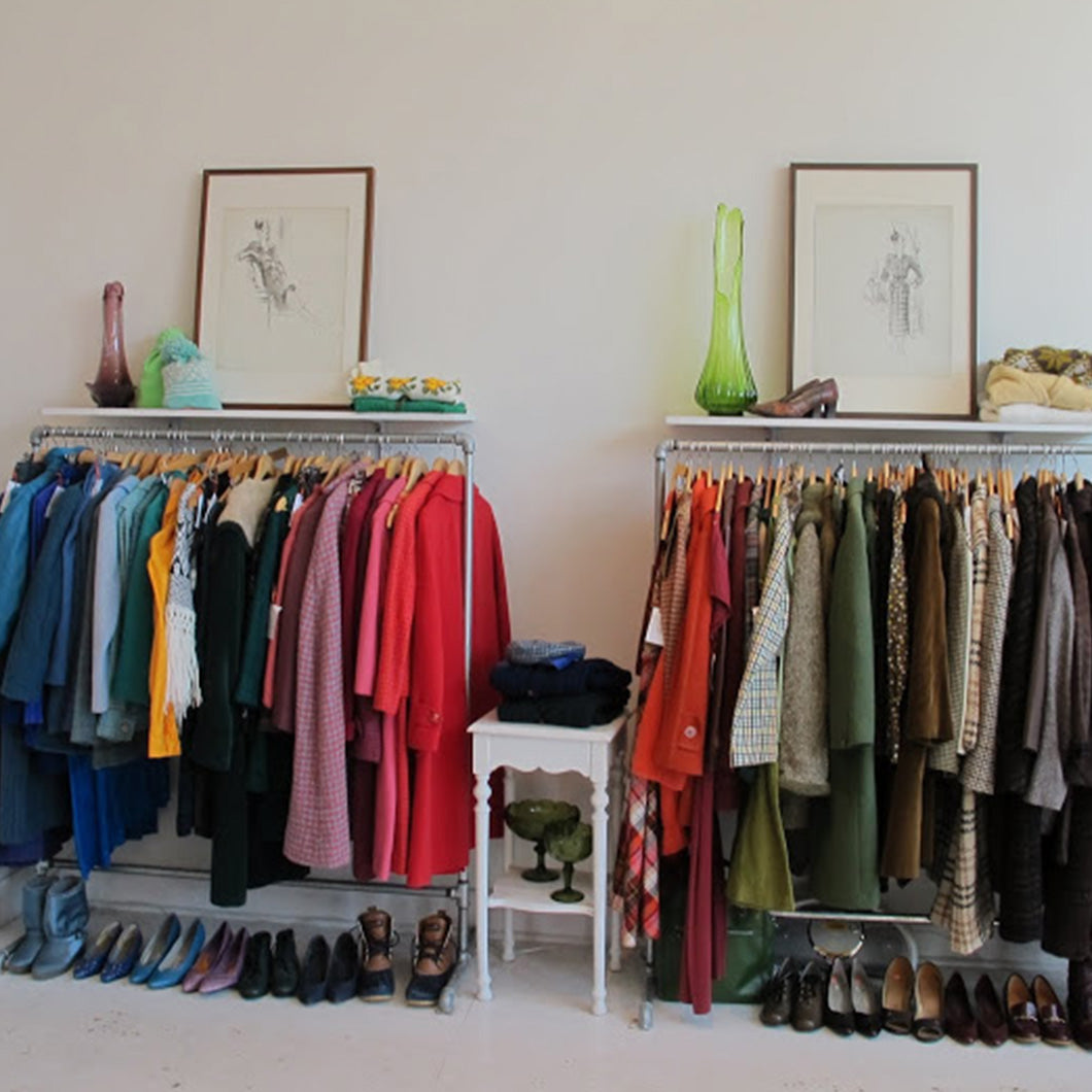 Racks of multicolored clothes and shoes stand in front of the white-walled interior of Clementine.