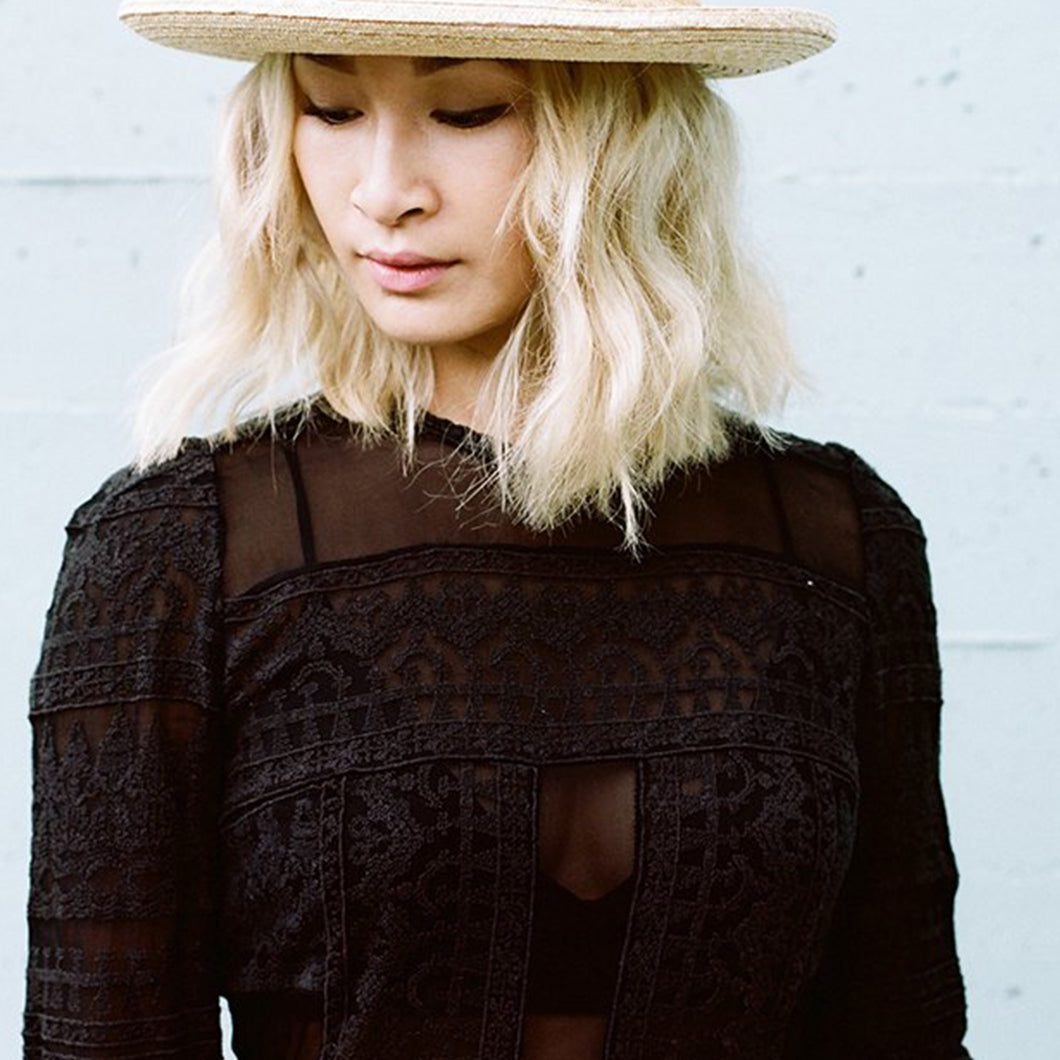 Cecilia wearing a black top and woven hat.